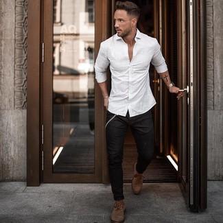 Cómo combinar: camisa de manga larga de rayas verticales blanca, vaqueros pitillo negros, botas casual de cuero marrónes
