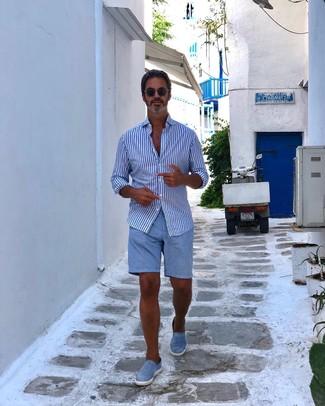 Cómo combinar: camisa de manga larga de rayas verticales en blanco y azul, pantalones cortos celestes, zapatillas slip-on celestes