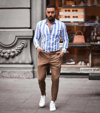 Cómo combinar: camisa de manga larga de rayas verticales en blanco y azul, pantalón chino marrón, tenis de cuero blancos, gafas de sol marrónes