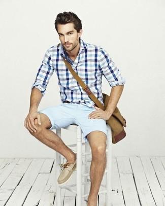 Cómo combinar: camisa de manga larga de cuadro vichy en blanco y azul, pantalones cortos celestes, náuticos de cuero en beige, bolso mensajero de lona marrón claro