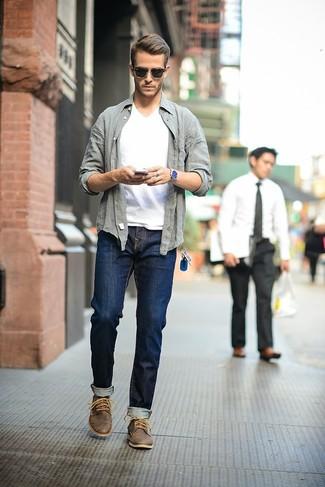 Emparejar una camisa de manga larga gris y unos vaqueros azul marino es una opción cómoda para hacer diligencias en la ciudad. Completa el look con botas safari de cuero en marrón oscuro.