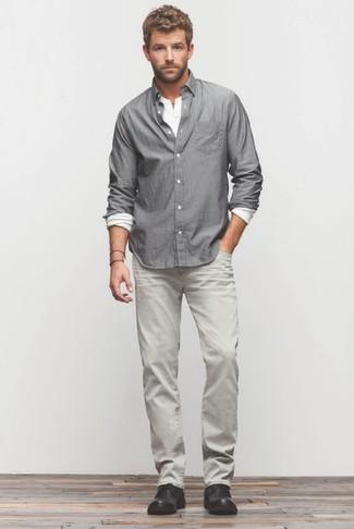 Cómo combinar: camisa de manga larga gris, camiseta henley de manga larga blanca, vaqueros grises, botas safari de cuero negras