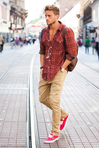 Una camisa de manga larga de tartán naranja y unos pantalones son prendas que debes tener en tu armario. Tenis rosa contrastarán muy bien con el resto del conjunto.