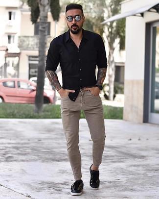 Cómo combinar: camisa de manga larga negra, vaqueros pitillo en beige, tenis de cuero negros, gafas de sol plateadas