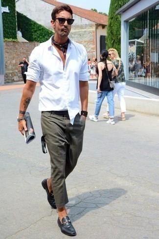 Cómo combinar un pantalón chino verde oscuro: Opta por una camisa de manga larga blanca y un pantalón chino verde oscuro para un almuerzo en domingo con amigos. ¿Por qué no ponerse mocasín de cuero negro a la combinación para dar una sensación más clásica?