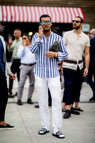 Cómo combinar: camisa de manga larga de rayas verticales en blanco y azul, pantalón chino blanco, sandalias de cuero estampadas en negro y blanco, bolso con cremallera de lona de camuflaje verde oliva