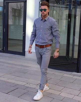 Cómo combinar: camisa de manga larga de cambray gris, pantalón chino gris, tenis de cuero blancos, correa de cuero en tabaco