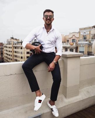 Cómo combinar un pantalón chino de rayas verticales negro: Utiliza una camisa de manga larga blanca y un pantalón chino de rayas verticales negro para cualquier sorpresa que haya en el día. Tenis de cuero estampados blancos son una opción incomparable para completar este atuendo.