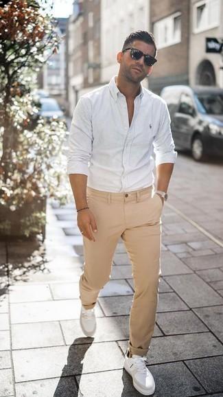 Cómo combinar un pantalón chino marrón claro: Opta por una camisa de manga larga de rayas verticales blanca y un pantalón chino marrón claro para conseguir una apariencia relajada pero elegante. Tenis de cuero blancos son una opción muy buena para completar este atuendo.