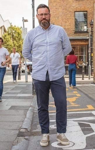 Moda para hombres de 40 años en clima cálido: Usa una camisa de manga larga de rayas verticales en blanco y azul y un pantalón chino azul marino para un almuerzo en domingo con amigos. Tenis de lona marrón claro son una opción inmejorable para complementar tu atuendo.
