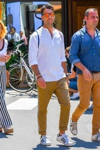 Cómo combinar unos tenis de cuero en blanco y azul marino: Equípate una camisa de manga larga blanca junto a un pantalón chino marrón claro para cualquier sorpresa que haya en el día. ¿Por qué no añadir tenis de cuero en blanco y azul marino a la combinación para dar una sensación más relajada?