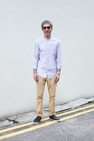 Moda para hombres de 40 años: Intenta combinar una camisa de manga larga celeste junto a un pantalón chino marrón claro para un look diario sin parecer demasiado arreglada. Tenis de lona negros añadirán un nuevo toque a un estilo que de lo contrario es clásico.