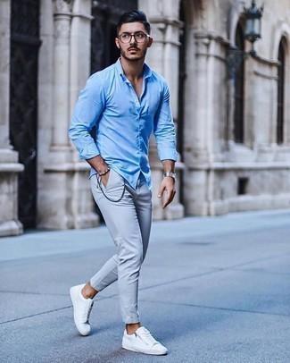 Cómo combinar un pantalón chino gris: Para un atuendo que esté lleno de caracter y personalidad intenta combinar una camisa de manga larga celeste con un pantalón chino gris. ¿Quieres elegir un zapato informal? Haz tenis de lona blancos tu calzado para el día.