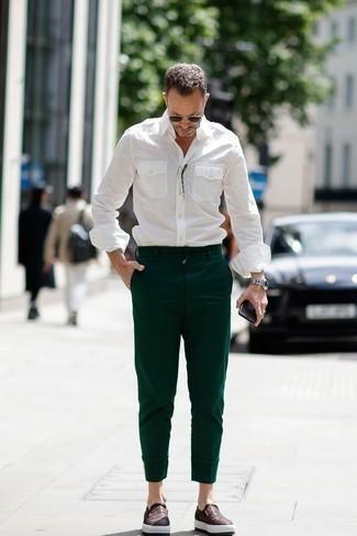 Outfits hombres: Equípate una camisa de manga larga blanca junto a un pantalón chino verde oscuro para un look diario sin parecer demasiado arreglada. Zapatillas slip-on de cuero en marrón oscuro son una opción atractiva para completar este atuendo.