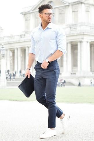 Cómo combinar: camisa de manga larga celeste, pantalón de vestir azul marino, tenis blancos, bolso con cremallera de cuero negro