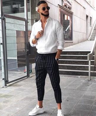 Cómo combinar: camisa de manga larga de lino blanca, pantalón de vestir de rayas verticales negro, tenis de cuero blancos, gafas de sol negras