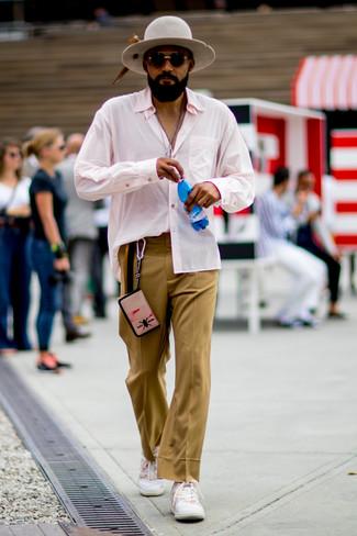 Cómo combinar: camisa de manga larga rosada, pantalón de vestir marrón claro, tenis blancos, sombrero de lana gris