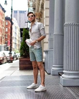 Cómo combinar: camisa de manga larga de lino blanca, pantalones cortos estampados en verde menta, tenis de lona blancos, gafas de sol negras