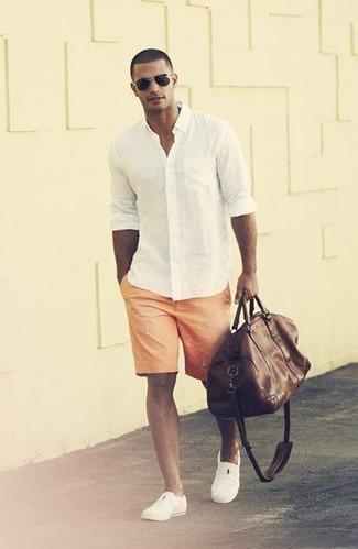 Cómo combinar: camisa de manga larga blanca, pantalones cortos estampados naranjas, zapatillas slip-on blancas, bolso baúl de cuero en marrón oscuro