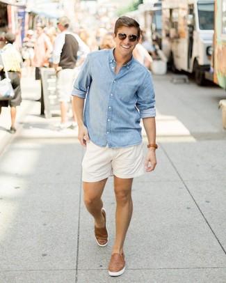 Cómo combinar: camisa de manga larga de cambray celeste, pantalones cortos blancos, zapatillas slip-on de cuero tejidas marrónes, gafas de sol en marrón oscuro