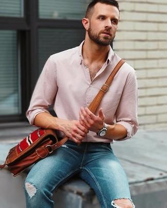 Cómo combinar: camisa de manga larga de lino rosada, vaqueros pitillo desgastados azules, bolso mensajero de cuero marrón, reloj plateado