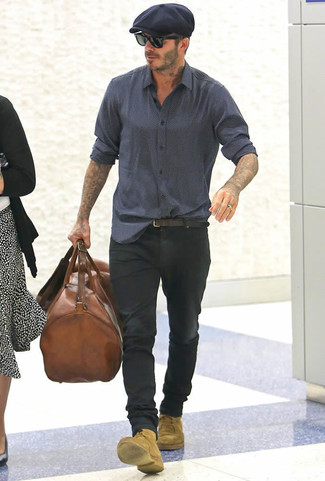 Look de David Beckham: Camisa de Manga Larga Estampada Azul Marino, Vaqueros Negros, Botas Casual de Ante Marrón Claro, Bolsa de Viaje de Cuero Marrón