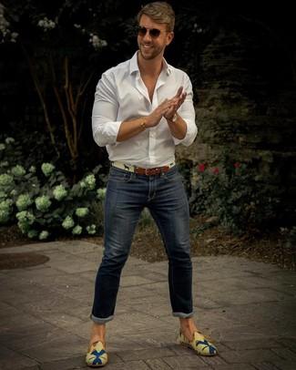 Cómo combinar: camisa de manga larga blanca, vaqueros pitillo azul marino, mocasín de lona estampado en multicolor, correa de lona en beige
