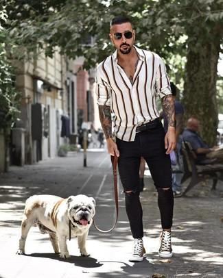 Cómo combinar: camisa de manga larga de rayas verticales blanca, vaqueros pitillo desgastados negros, zapatillas altas de lona verde oliva, correa de cuero negra