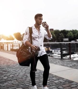 Cómo combinar: camisa de manga larga estampada en blanco y negro, vaqueros pitillo desgastados negros, zapatos derby de cuero blancos, bolsa de viaje de cuero en marrón oscuro