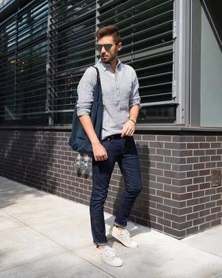 Cómo combinar: camisa de manga larga de lino de rayas verticales en blanco y azul marino, vaqueros azul marino, tenis de lona en beige, bolsa tote de lona azul marino