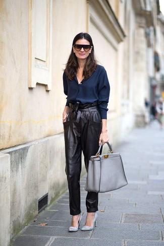 Cómo combinar: camisa de vestir azul marino, pantalón de pinzas de cuero negro, zapatos de tacón de cuero grises, bolsa tote de cuero gris