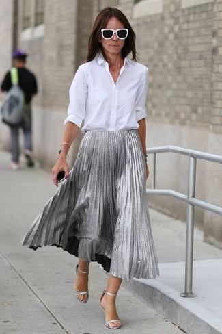 Cómo combinar: camisa de vestir blanca, falda midi plisada plateada, sandalias de tacón de cuero plateadas, gafas de sol en negro y blanco