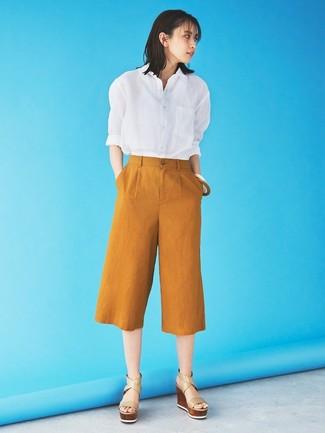 Cómo combinar: camisa de vestir blanca, falda pantalón en tabaco, sandalias con cuña de cuero en beige