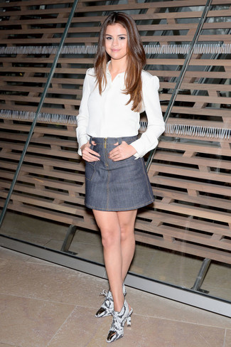 Look de Selena Gomez: Camisa de Vestir Blanca, Minifalda Vaquera Gris, Botines de Cuero con print de serpiente Grises