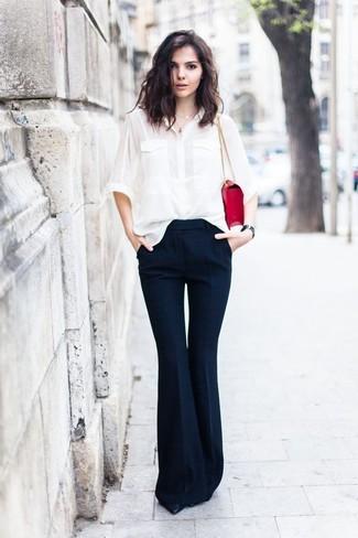 Cómo combinar: camisa de vestir de seda blanca, pantalón de campana azul marino, zapatos de tacón de cuero negros, bolso de hombre de cuero rojo