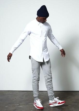 Cómo combinar: camisa de vestir blanca, pantalón de chándal gris, deportivas de ante rojas, gorro negro