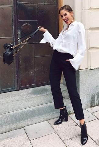 Cómo combinar: camisa de vestir blanca, pantalón de pinzas negro, botines de cuero negros, bolso bandolera de cuero acolchado negro