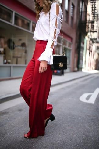 Cómo combinar: camisa de vestir con recorte blanca, pantalones anchos rojos, sandalias de tacón de cuero negras, bolso bandolera de cuero negro