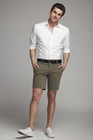 Cómo combinar: camisa de vestir blanca, pantalones cortos verde oliva, tenis de lona blancos, correa de cuero negra