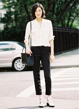 Cómo combinar: camisa de vestir blanca, pantalones pitillo negros, botines de cuero con recorte blancos, bolso bandolera de cuero negro