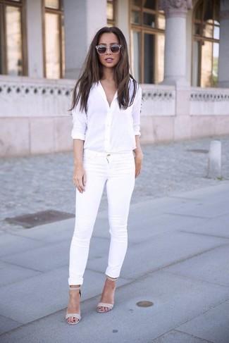 Cómo combinar: camisa de vestir blanca, vaqueros pitillo blancos, sandalias de tacón de cuero grises, gafas de sol grises