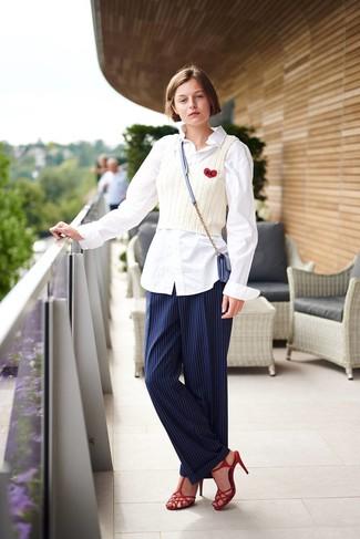 Cómo combinar: camisa de vestir blanca, camiseta sin manga de punto blanca, pantalón de vestir de rayas verticales azul marino, sandalias de tacón de cuero rojas