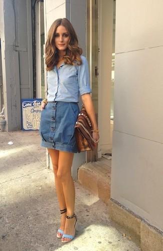 Cómo combinar: camisa de vestir de cambray celeste, falda con botones vaquera azul, sandalias de tacón de cuero celestes, cartera sobre de cuero marrón