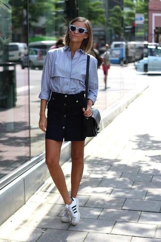 Cómo combinar: camisa de vestir de rayas verticales celeste, falda con botones negra, tenis de cuero en blanco y negro, bolso bandolera de cuero negro