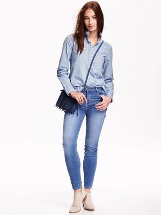 Cómo combinar: camisa de vestir de cambray celeste, vaqueros pitillo azules, botines de ante en beige, bolso bandolera de cuero azul