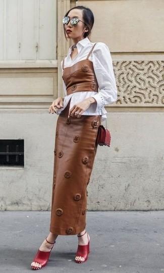 Cómo combinar: camisa de vestir blanca, corsé de cuero marrón, falda larga de cuero marrón, sandalias de tacón de cuero rojas
