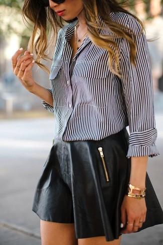 Cómo combinar una camisa de vestir de rayas verticales en negro y blanco: Para un atuendo que esté lleno de caracter y personalidad ponte una camisa de vestir de rayas verticales en negro y blanco y una falda skater de cuero negra.