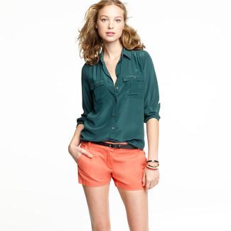Considera emparejar una camisa de vestir de seda verde oscuro con unos pantalones cortos naranjas para un almuerzo en domingo con amigos.