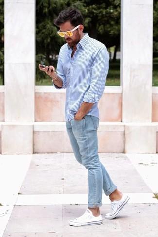 Cómo combinar: camisa de vestir de rayas verticales en blanco y azul, vaqueros pitillo celestes, tenis blancos, gafas de sol amarillas