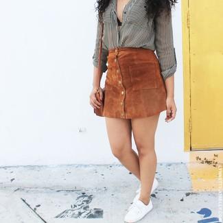 Cómo combinar: camisa de vestir de rayas verticales en blanco y negro, falda con botones de ante marrón, tenis de lona blancos, bolso bandolera de cuero marrón